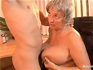 Mature plumper takes a load on her gigantic natural boobs